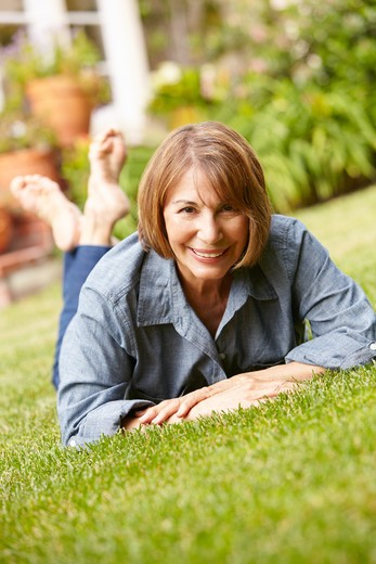 Stock Photo: 1888R-43232 Mid age woman relaxing in garden