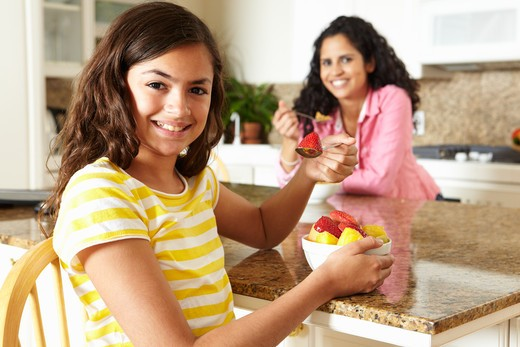 Mother and daughter eating cereal and fruit : Stock Photo