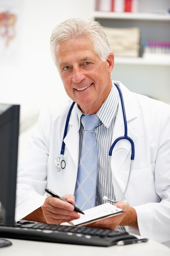 Senior doctor at desk : Stock Photo