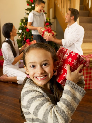 Hispanic family exchanging gifts at Christmas : Stock Photo