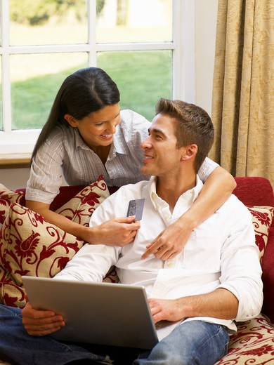 Young Hispanic couple shopping online : Stock Photo
