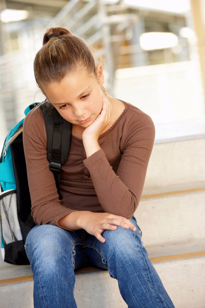 Unhappy Pre teen girl in school : Stock Photo