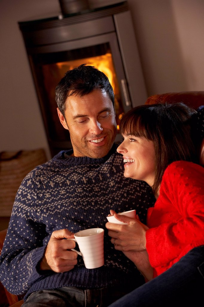 Middle Aged Couple Sitting On Sofa By Cosy Log Fire With Hot Drink : Stock Photo