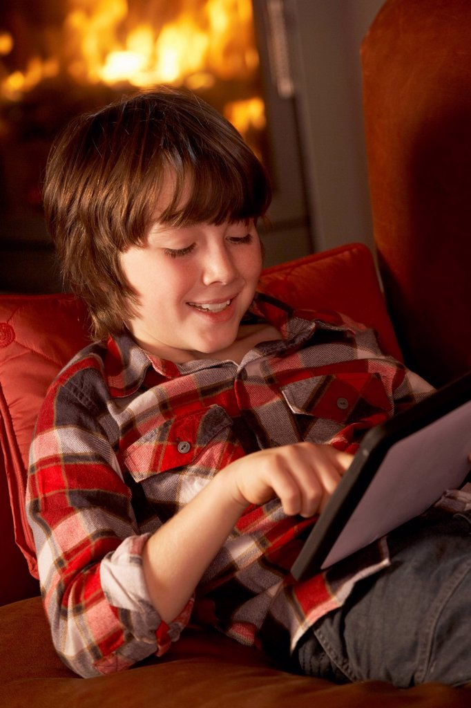 Young Boy Relaxing With Tablet Computer By Cosy Log Fire : Stock Photo