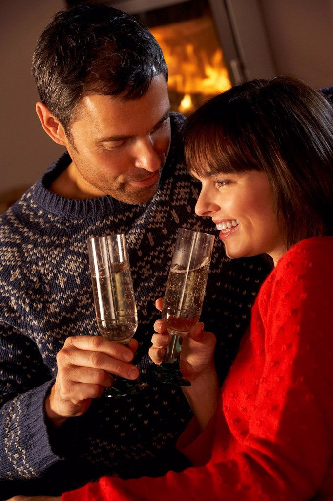 Stock Photo: 1888R-44442 Middle Aged Couple Sitting Sofa By Cosy Log Fire With Glass Of Champagne