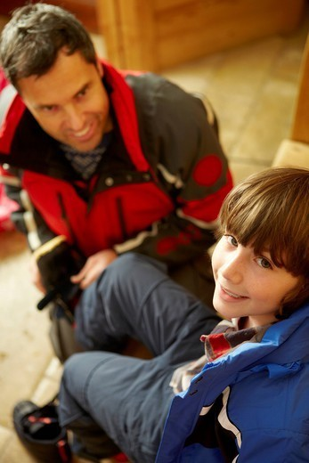Father Helping Son To Put On Warm Outdoor Clothes And Boots : Stock Photo