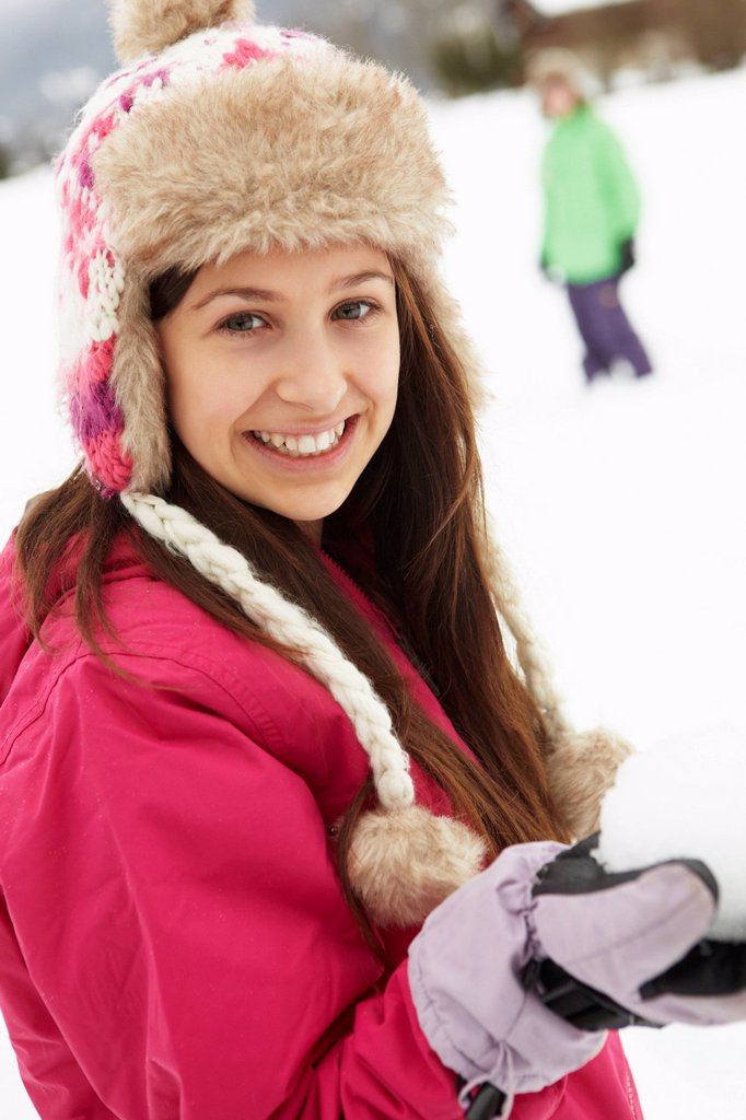 Stock Photo: 1888R-44530 Teenage Couple Having Snowball Fight Wearing Fur Hats