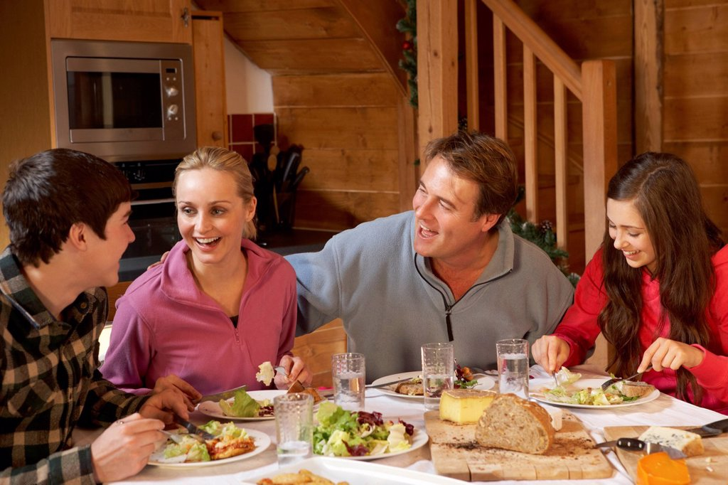 Stock Photo: 1888R-44712 Teenage Family Enjoying Meal In Alpine Chalet Together