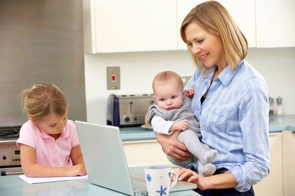 Stock Photo: 1888R-44946 Mother with children using laptop in kitchen