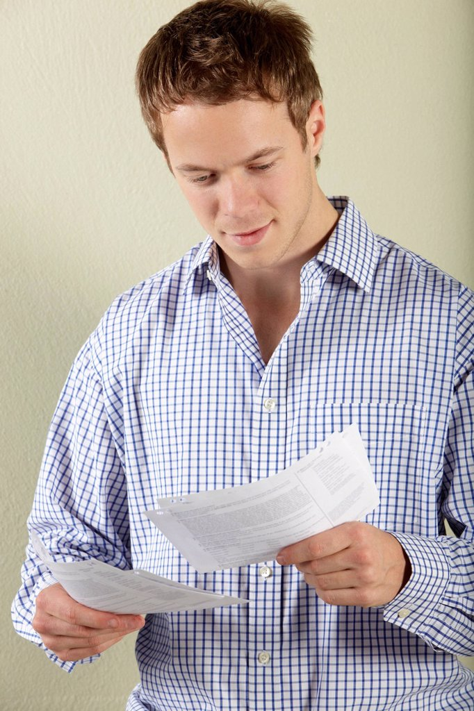 Studio Shot Of Young Man Looking at Bills : Stock Photo
