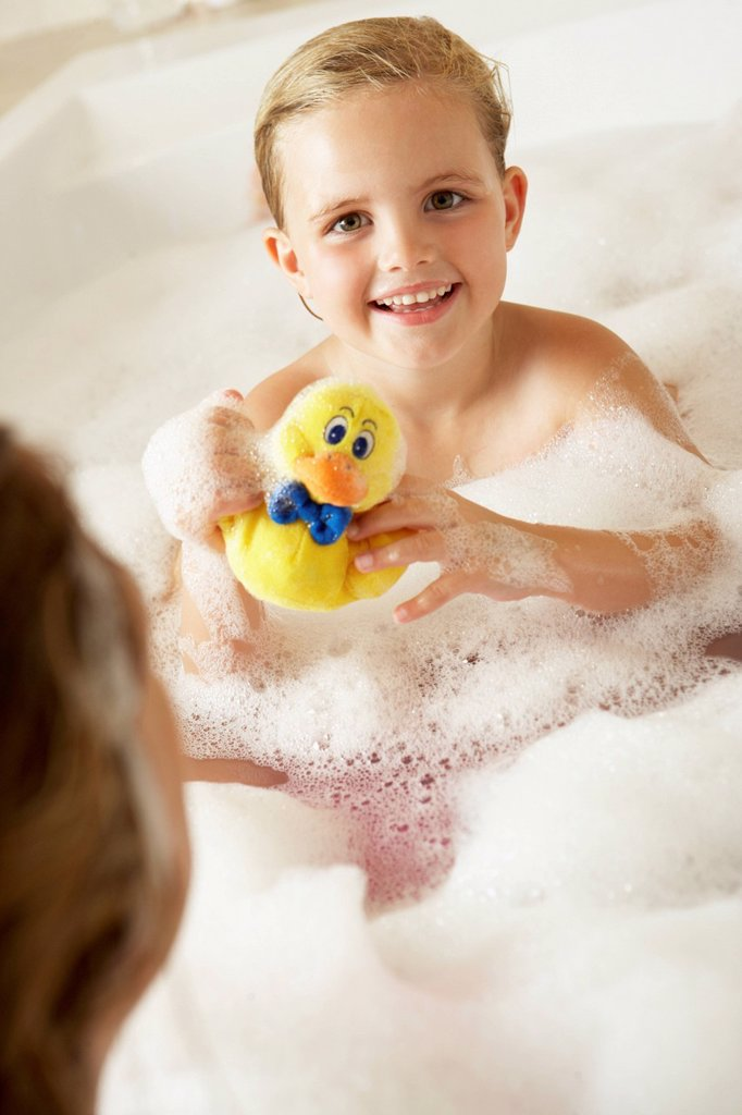 Mother And Daughter Relaxing In Bubble Filled Bath : Stock Photo