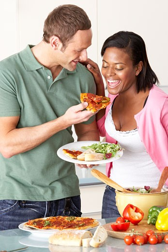 Young Couple Eating Meal In Kitchen : Stock Photo
