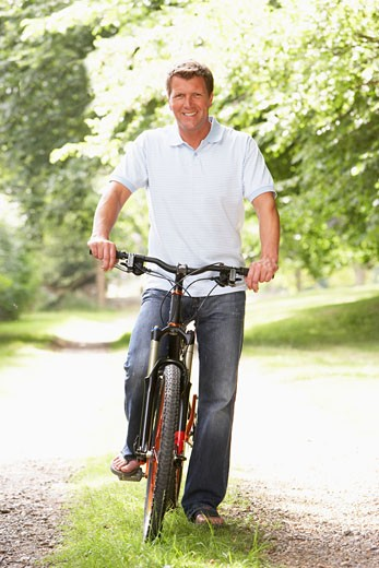 Young man riding bike in countryside : Stock Photo