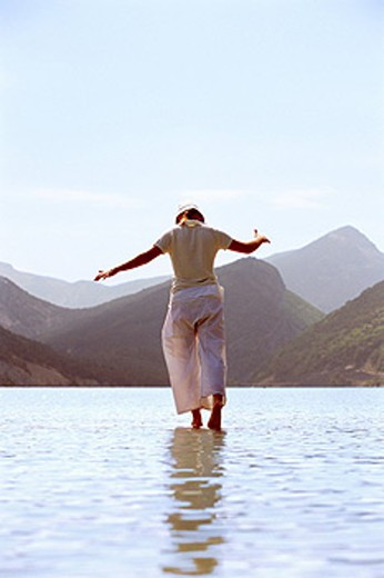 Woman outdoors walking on water in scenic location : Stock Photo
