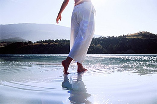 Woman´s legs outdoors walking on water in scenic location lens flare : Stock Photo