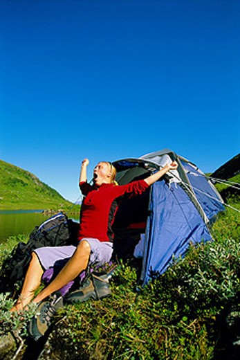Stock Photo: 1888R-8574 Woman outdoors at campsite by lake yawning and stretching