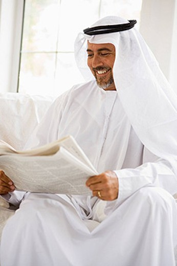Man sitting indoors with newspaper smiling high key/selective focus : Stock Photo