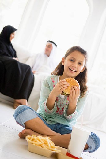 Young girl with fast food in living room smiling with parents in background high key/selective focus : Stock Photo
