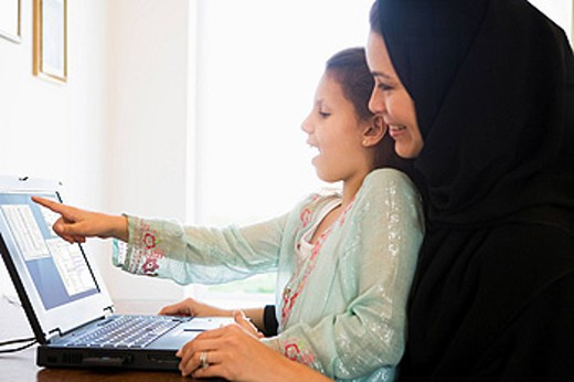 Mother and daughter in office with laptop pointing and smiling high key/selective focus : Stock Photo