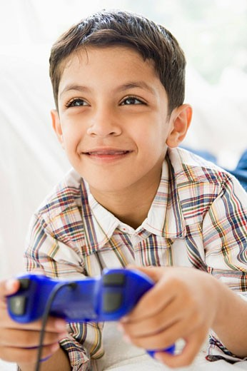 Stock Photo: 1888R-8720 Young boy in living room playing video games and smiling high key/selective focus