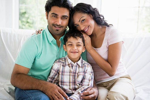 Stock Photo: 1888R-8748 Family in living room sitting on sofa smiling high key