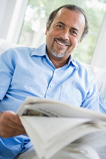 Stock Photo: 1888R-8773 Man in living room with newspaper smiling high key/selective focus