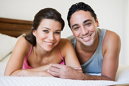 Stock Photo: 1888R-8801 Couple relaxing on bed in bedroom smiling selective focus