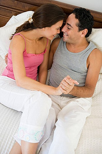 Stock Photo: 1888R-8806 Couple relaxing on bed holding hands in bedroom smiling selective focus