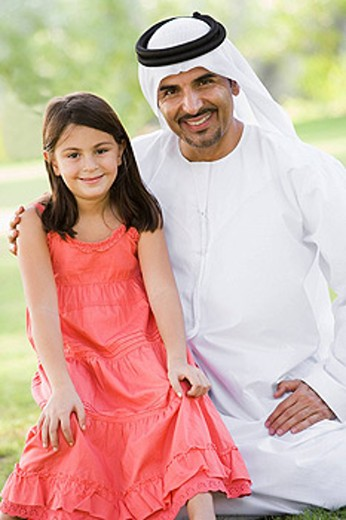 Man and young girl outdoors in a park smiling selective focus : Stock Photo