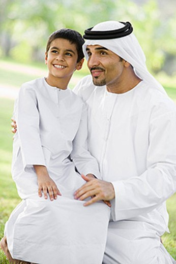 Man and young boy outdoors in a park smiling selective focus : Stock Photo