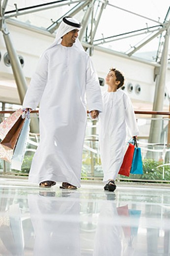 Man and young boy walking in mall holding hands and smiling selective focus : Stock Photo