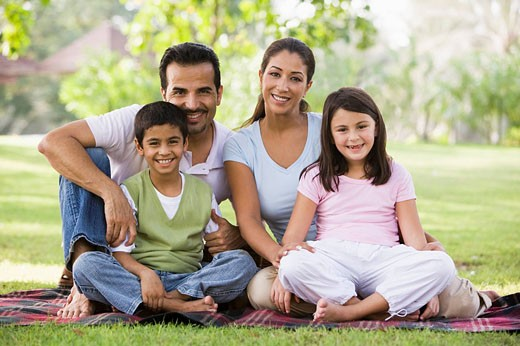 Family sitting outdoors in park smiling selective focus : Stock Photo