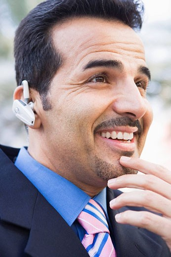 Businessman outdoors wearing headset and smiling selective focus : Stock Photo