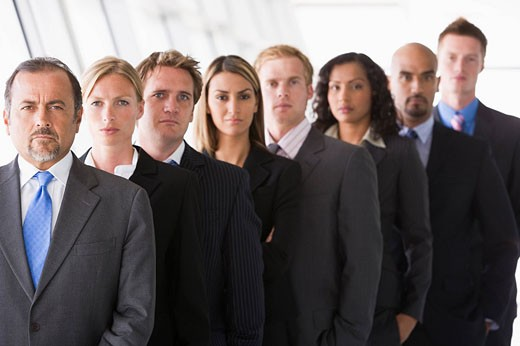 Group of co_workers standing in office space smiling high key/depth of field : Stock Photo