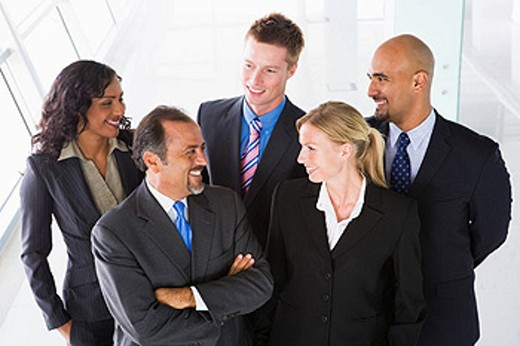 Group of co_workers standing in office space smiling high key : Stock Photo