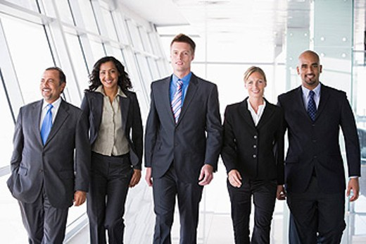 Group of co_workers walking in office space smiling high key : Stock Photo