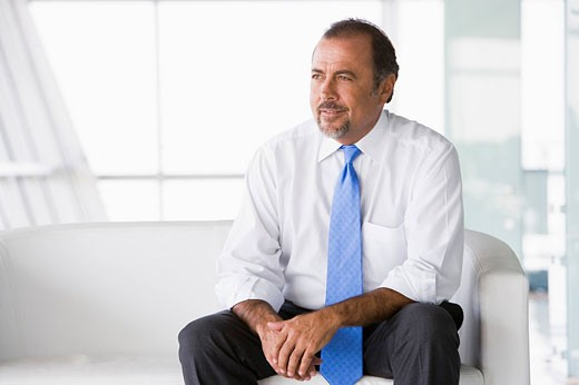 Stock Photo: 1888R-9353 Businessman sitting indoors high key/selective focus