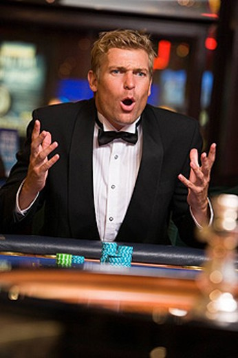 Stock Photo: 1888R-9529 Man in casino playing roulette and losing selective focus