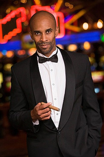Man in casino smoking cigar selective focus : Stock Photo