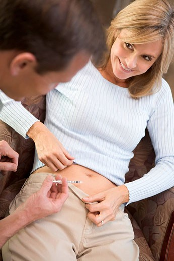 Man helping woman inject drugs to prepare for IVF treatment selective focus : Stock Photo