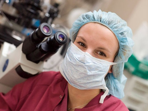Embryologist sitting by microscope with mask on selective focus : Stock Photo