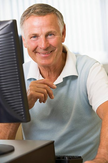Man sitting at a computer terminal high key : Stock Photo