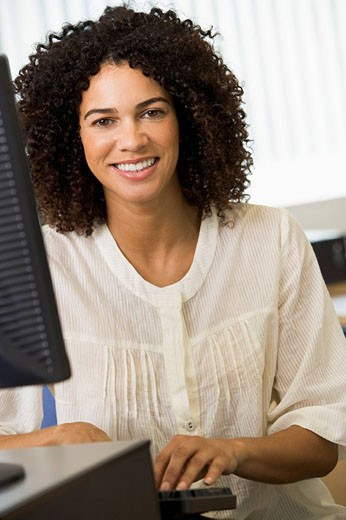 Woman sitting at a computer terminal typing high key : Stock Photo
