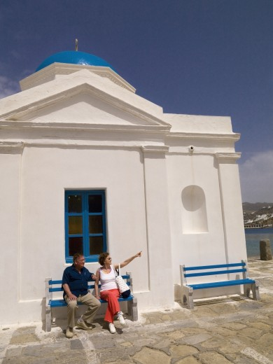 Senior couple sitting outside orthodox church; Mykonos, Greece : Stock Photo