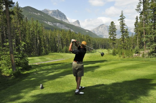 Mid-adult man playing golf; Canmore, Alberta's Rockies, Alberta, Canada : Stock Photo