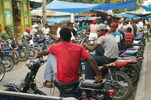Motorcycle taxi waiting for passenger at street market; Neiba, Baoruco, Dominican Republic : Stock Photo