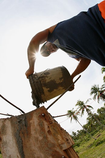 Tasbapauni, Nicaragua; Man pouring cement from bucket : Stock Photo