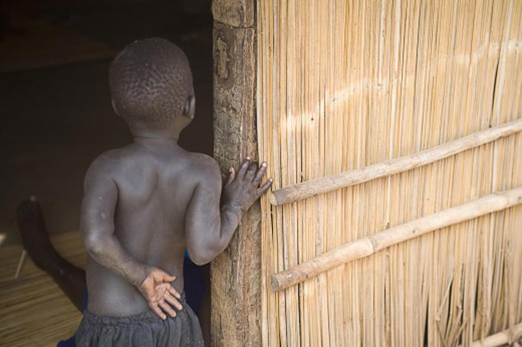Gulu, Northern Uganda; Young boy looking around door into house : Stock Photo