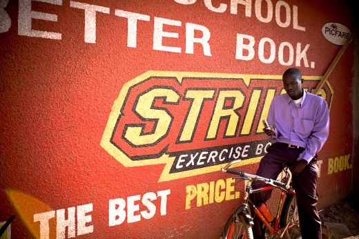 Gulu, Northern Uganda; Man sitting on bicycle beside sign, text messaging on mobile phone : Stock Photo