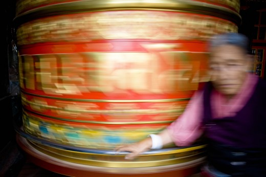 Stock Photo: 1889-43179 Boudhanath, Kathmandu, Nepal; Woman spinning mani wheel